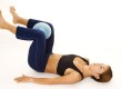 A female fitness instructor demonstrates an abductor squeeze - Exercise